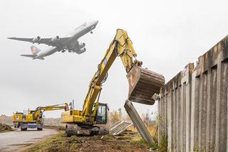 Abriss der Mauer mit Flugzeug am Himmel